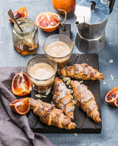 Traditional Italian style home breakfast  Latte in glasses  almond croissants and red bloody Sicilian oranges over concrete textured table