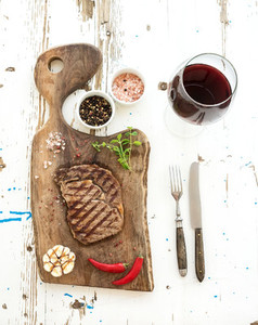 Grilled ribeye beef steak with herbs  spices  and glass of red wine on walnut cutting board over white rustic wooden background