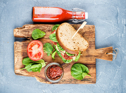 Chicken sun dried tomato and spinach sandwich with spicy sauce on rustic wooden board over grey concrete textured background