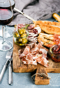 Meat appetizer selection  Salami  prosciutto  bread sticks  baguette  olives and sun dried tomatoes  two glasses of red wine over grey concrete textured backdrop
