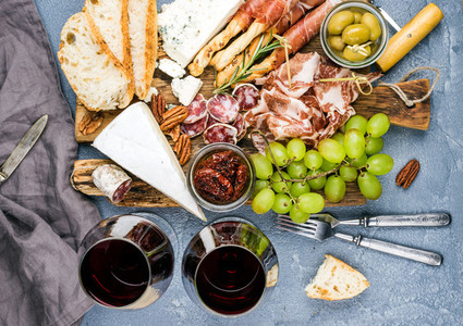 Cheese and meat appetizer selection  Prosciutto di Parma  salami  bread sticks  baguette slices  olives  sun dried tomatoes  grapes  nuts  red wine in glasses on rustic wooden board