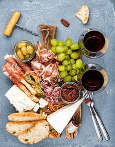 Cheese and meat appetizer selection or wine snack set  Variety of cheese  salami  prosciutto  bread sticks  baguette  honey  grapes  olives  sun dried tomatoes  pecan nuts over grey concrete textured