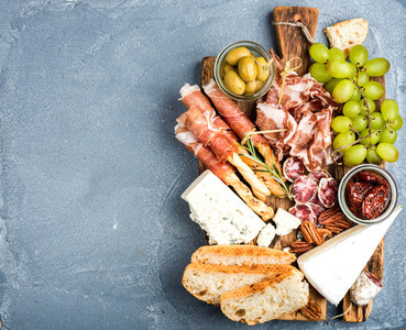 Cheese and meat appetizer selection  Prosciutto di Parma  salami  bread sticks  baguette slices  olives  sun dried tomatoes  grapes nuts on rustic wooden board
