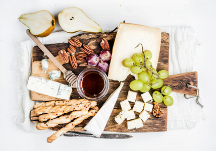Cheese appetizer set Various types of cheese honey grapes pear nuts and bread grissini sticks on rustic wooden board over white background