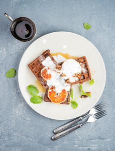 Belgian soft waffles with blood orange cream marple syrup and mint  on white plates