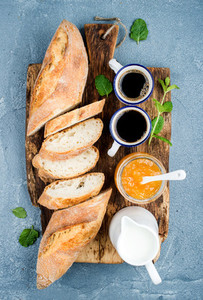 Breakfast set  Baguette  orange jam and coffee in cups on rustic wooden board over concrete grey blue background