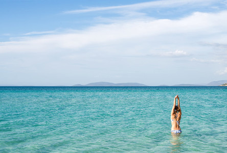 Back of beautiful woman wearing blue bikini standing in the water on Mediterranean sea coast  Cesme  Ilica beach  Turkey