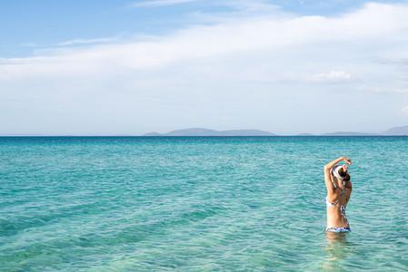 Back of beautiful woman wearing blue bikini standing in the water on Mediterranean sea coast  Cesme  Ilica beach  Turkey