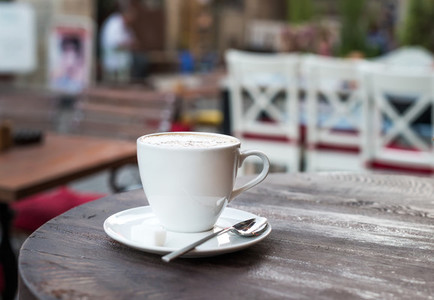 Cup of cappuccino on old dark wooden table in a street cafe