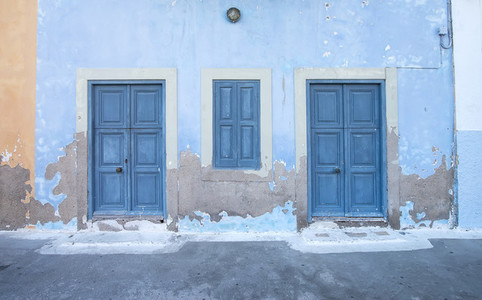 Mediterranean style exterior Blue wooden doors and window shutters old painted wall on a Greek island