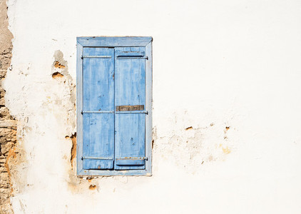 Mediterranean style old window  Blue on light wall with closed shutters
