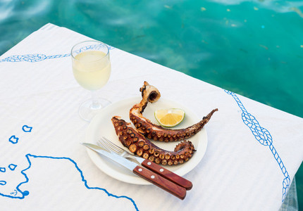 Grilled octopus and white wine glass on a table at the sea coast