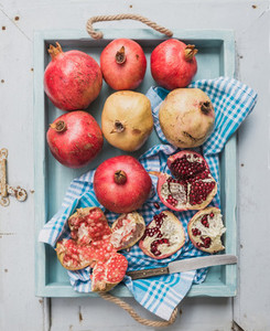 Red and white pomegranates with knife on kitchen towel in blue tray over light painted wooden backdrop