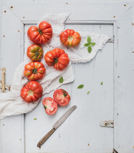 Fresh ripe hairloom tomatoes and basil on rustuc blue wooden surface
