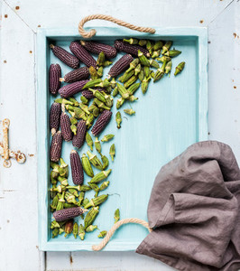 Okra and small black corns on blue wooden tray over light rustic backdrop  top view