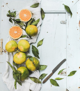 Fresh Turkish tangerines with leaves over blue rustic wooden backdrop  top view
