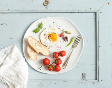 Breakfast set  Fried egg  bread slices  cherry tomatoes  hot peppers and herbs on white ceramic plate over light blue wooden backdrop  top view