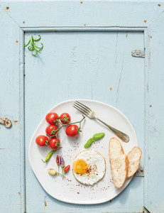 Breakfast set  Fried egg  bread slices  cherry tomatoes  hot peppers and herbs
