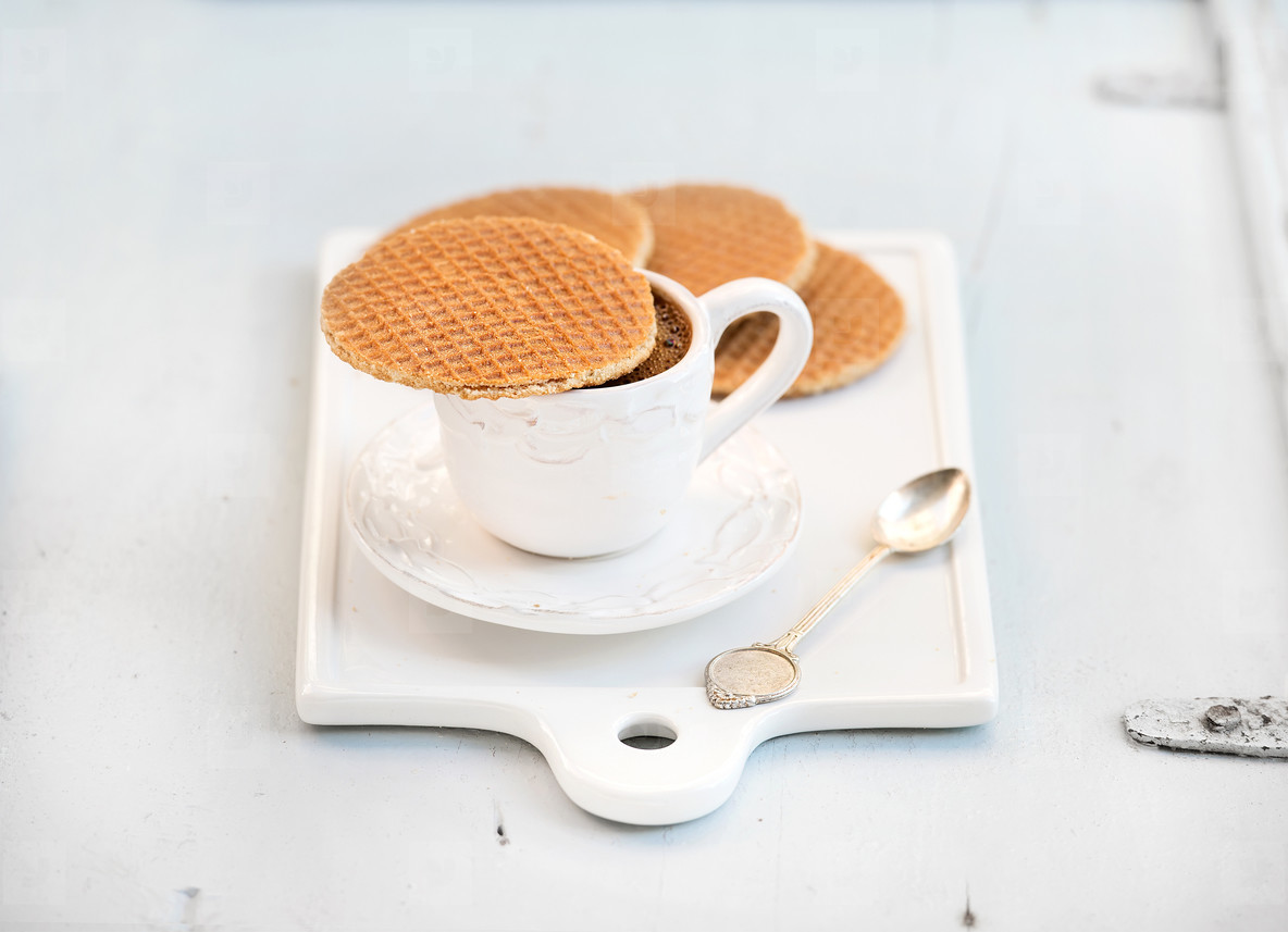 Dutch caramel stroopwafels and cup of black coffee on white ceramic serving board over light blue wooden backdrop
