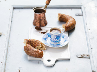 Turkish black coffee served in traditional ceramic cup with pattern  sesame bagel called simit on white serving board over light blue wooden background
