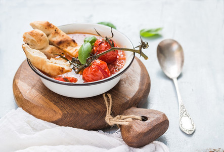 Italian tomato  garlic and basil soup Pappa al Pomodoro in metal bowl with bread on rustic wooden board over light blue background
