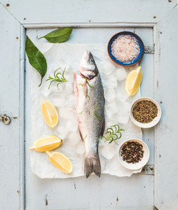 Fresh uncooked seabass fish with lemon herbs ice and spices on rustic blue wooden board backdrop