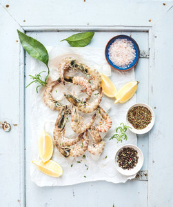Fresh uncooked shrimps with lemon  herbs  ice and spices on rustic blue wooden board backdrop