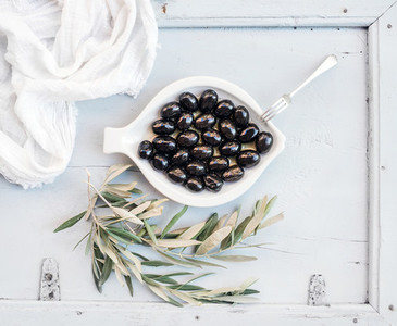 Black olives in white ceramic plate with tree branches  top view