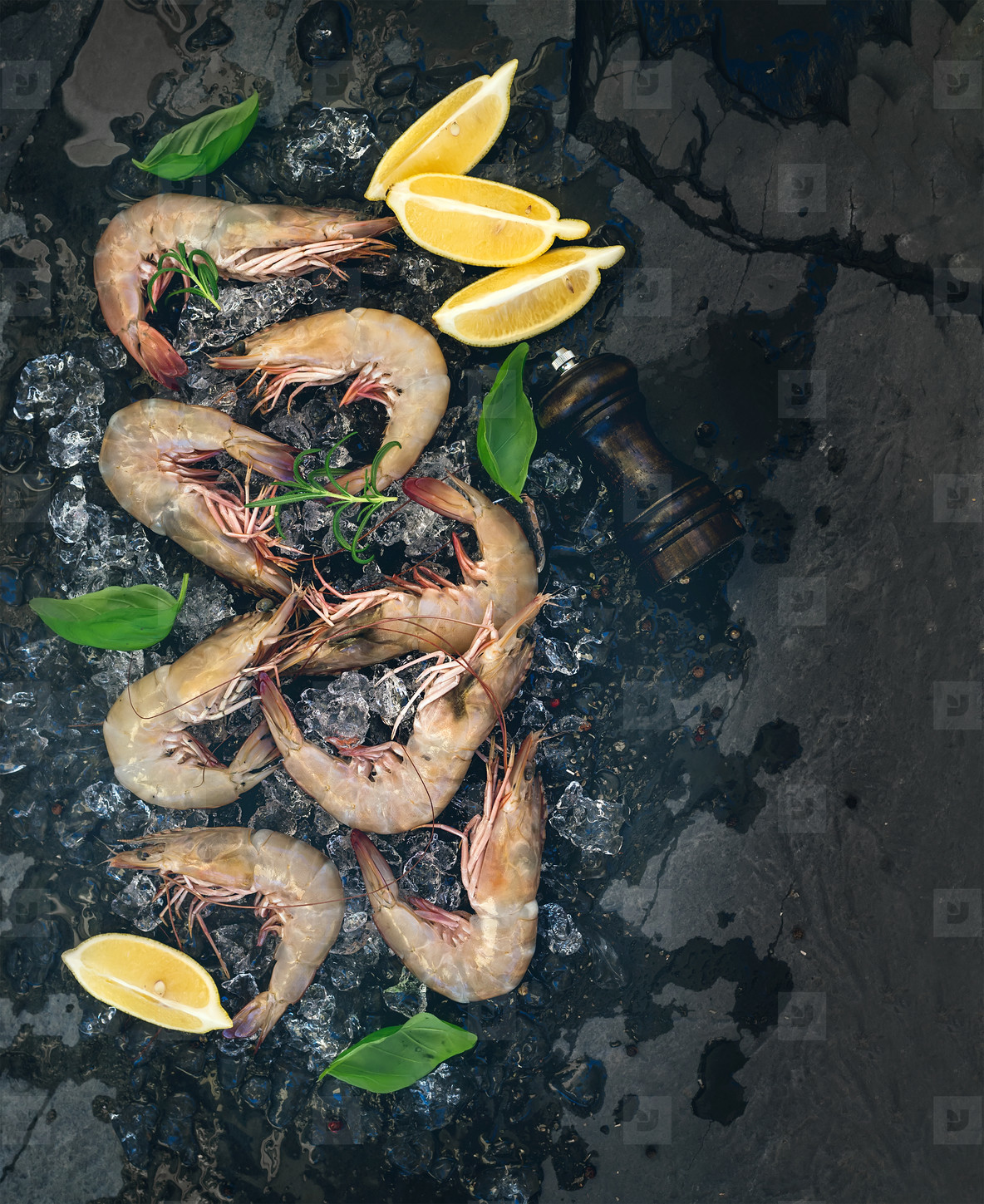 Fresh uncooked shrimps with lemon  herbs and spices on chipped ice over dark slate stone backdrop