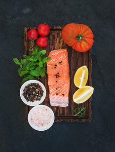 Ingredients  Raw salmon filet  lemon  cherry and heirloom tomatoes  fresh mint  spices on rustic wooden board over dark stone backdrop