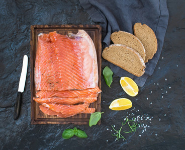 Smoked salmon filet with lemon  fresh herbs and bred on wooden serving board over dark stone backdrop