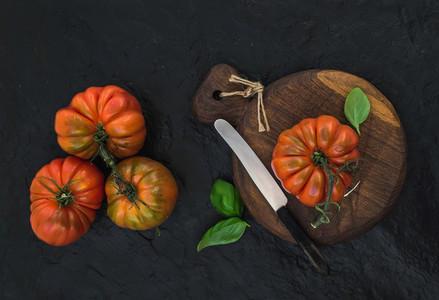 Fresh ripe hairloom tomatoes and basil leaves on rustic wooden board