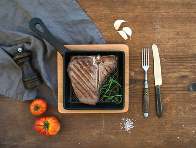Cooked meat t bone steak with garlic cloves  tomatoes  rosemary  pepper and salt in small cooking pan over rustic wooden background