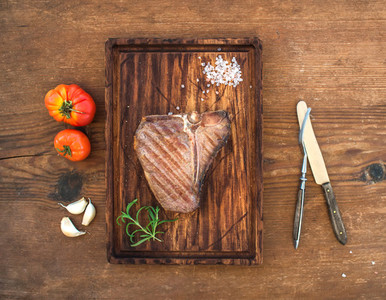 Cooked meat t bone steak on serving board with garlic cloves tomatoes rosemary and spices over rustic wooden background