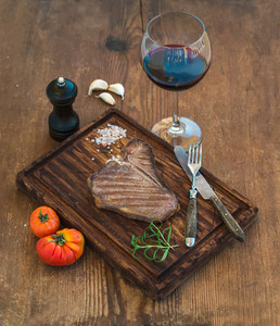 Cooked meat t bone steak on serving board with garlic cloves  tomatoes  rosemary  spices and glass of red wine over rustic wooden background