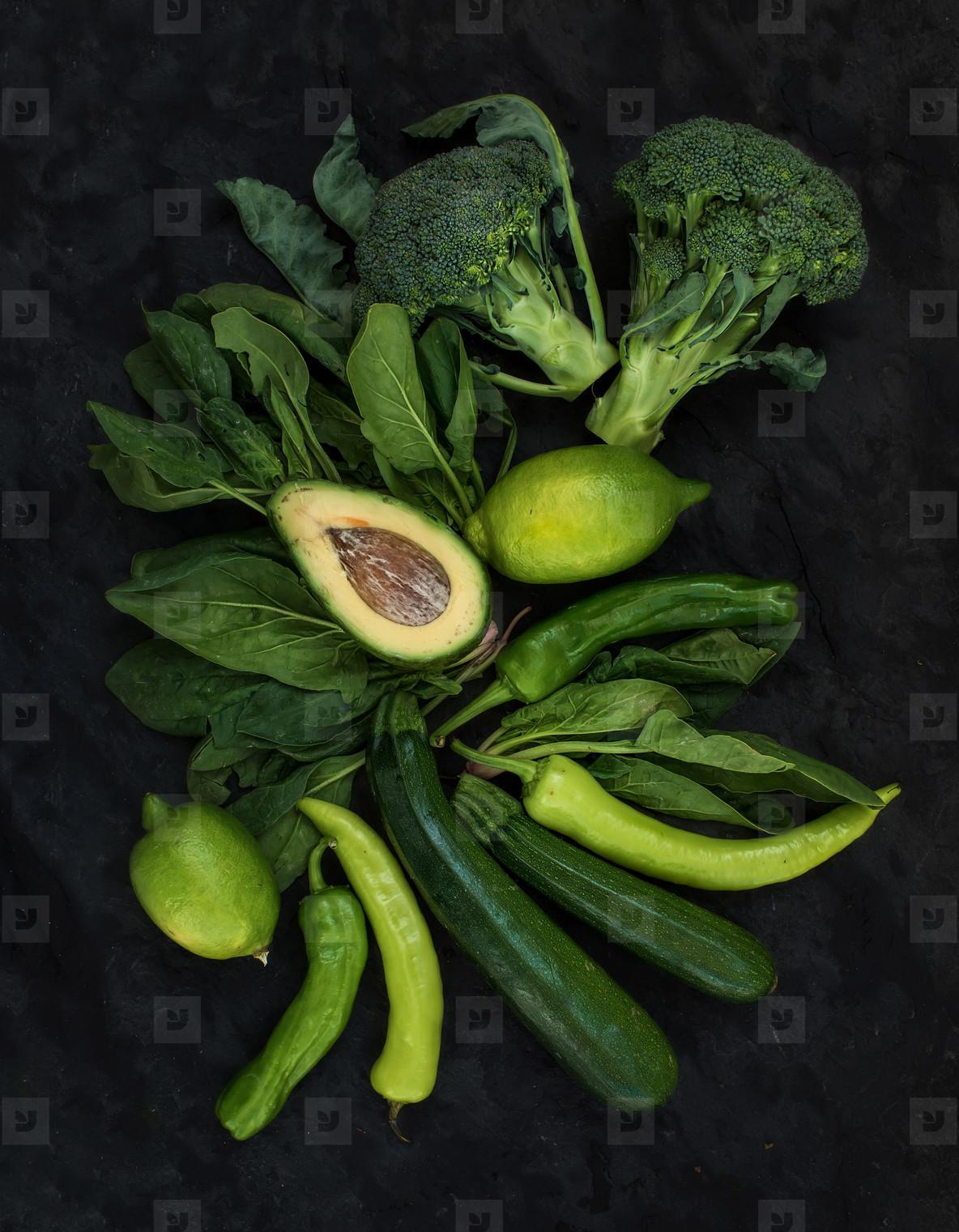 Raw green vegetables set  Broccoli  avocado  pepper  spinach  zucchini  lime on dark stone background