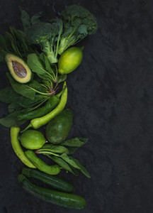 Raw green vegetables set Broccoli avocado pepper spinach zuccini lime on  dark stone background