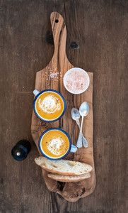 Homemade pumpkin cream soup in enamel mugs with herbs and fresh bread slices on olive serving board over rustic wooden background