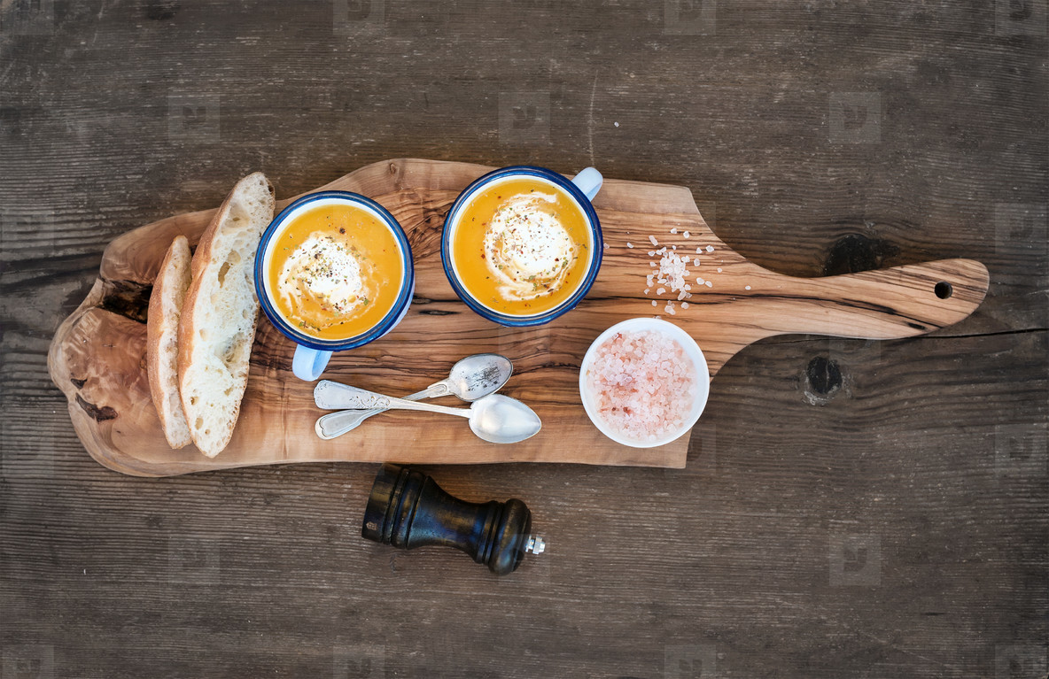 Homemade pumpkin cream soup in enamel mugs with herbs and fresh bread slices on olive serving board over rustic wooden background  horizontal