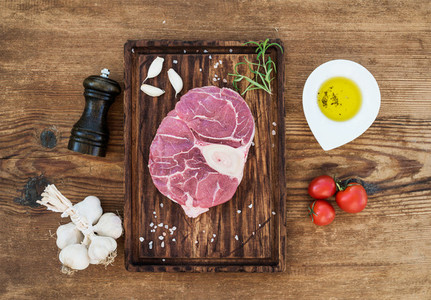 Raw fresh beef meat cross cut for ossobuco with garlic cloves cherry tomatoes rosemary pepper oil and salt on serving board over rustic wooden background