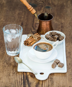 Cup of black coffee copper pot water with ice in glass cinnamon sticks and cane sugar cubes on white ceramic serving board over rustic wooden backdrop