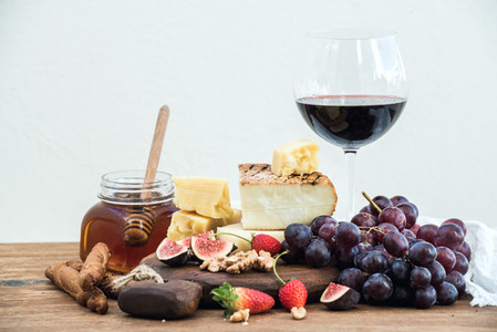 Glass of red wine cheese board grapesfig strawberries honey and bread sticks  on rustic wooden table white background
