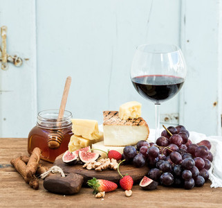 Glass of red wine  cheese board  grapes fig  strawberries  honey and bread sticks  on rustic wooden table  blue background