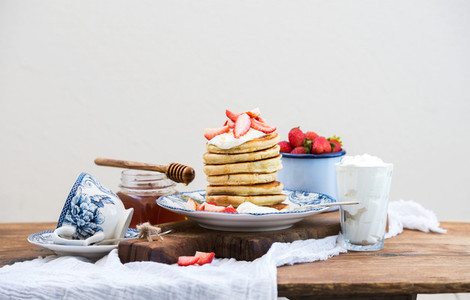 Breakfast set Pancakes with fresh strawberries sour cream and honey on a porcelain plate over rustic wooden table Blue enamel cup full of berries behind white background