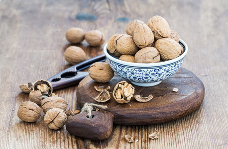 Walnuts in ceramic bowl and on cutting board with nutcracker over  rustic wooden background