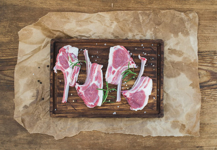Rack of Lamb with rosemary and spices on rustic chopping board over oily craft paper  old wooden background