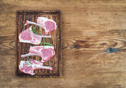 Rack of Lamb with rosemary and spices on rustic chopping board over old wooden background