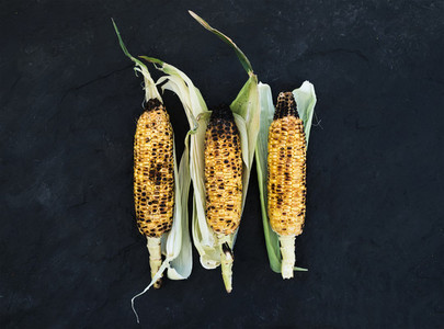Grilled corn over black slate stone background  top view