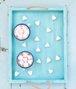 Saint Valentines holiday greeting set Hot chocolate and heart shaped marshmallows in old enamel mugs on turquoise serving tray over blue wooden background