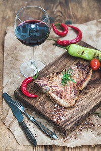 Cooked meat t bone steak on serving board with roasted tomatoes  chili peppers  fresh rosemary  spices and glass of red wine over rustic wooden background